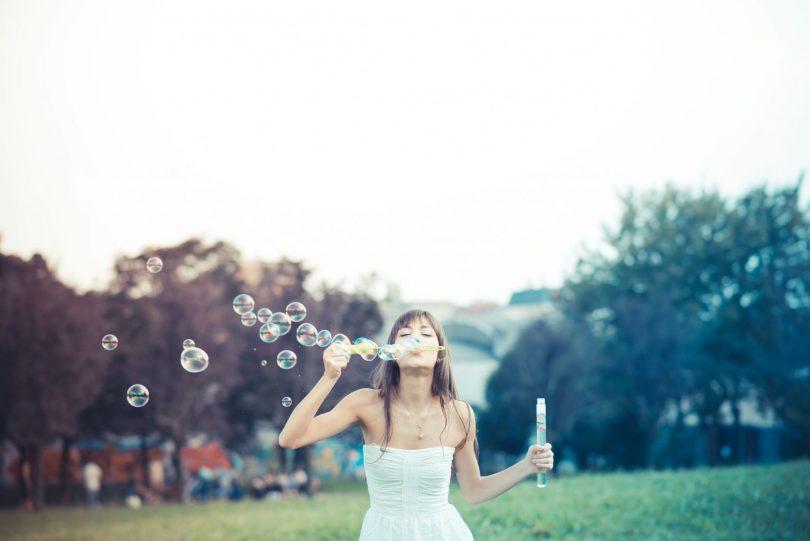 Mulher em campo gramado assoprando bolhas de sabão.