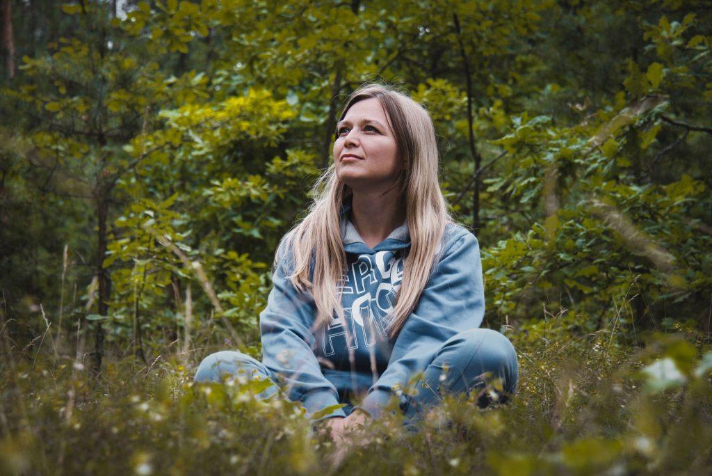 Mulher senta com as pernas cruzadas, observando a natureza, no meio de uma floresta.