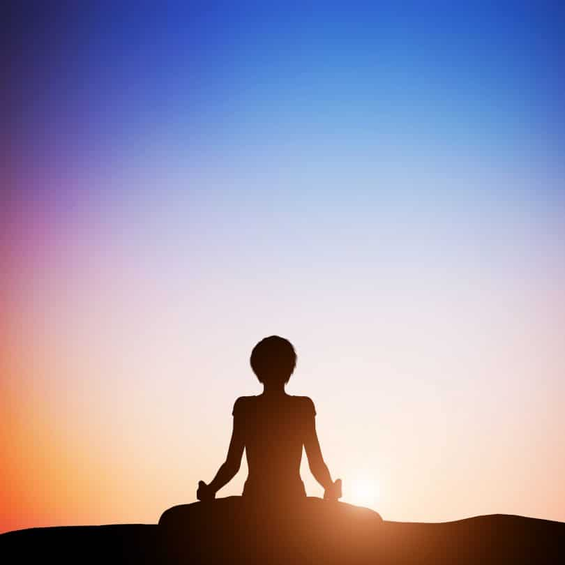 Silhueta de mulher sentada em posição de lótus, com as pernas cruzadas, meditando.