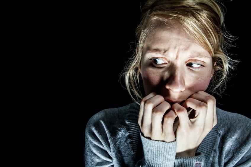 Mulher no escuro, com os dedos dobrado em frente a boca, olhando para o lado com expressão de medo.