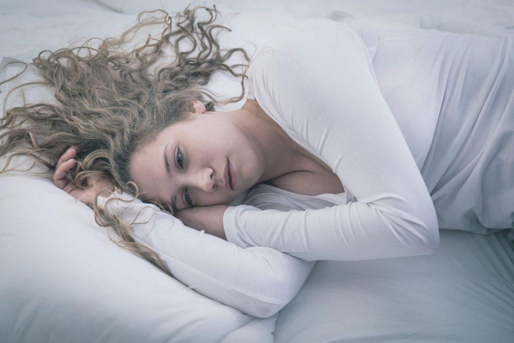 Mulher deitada com expressão triste e olhos de quem chorou recentemente.