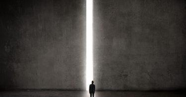 Homem parado em frente a parede gigante de concreto, com abertura no meio por onde passa um feixe de luz.