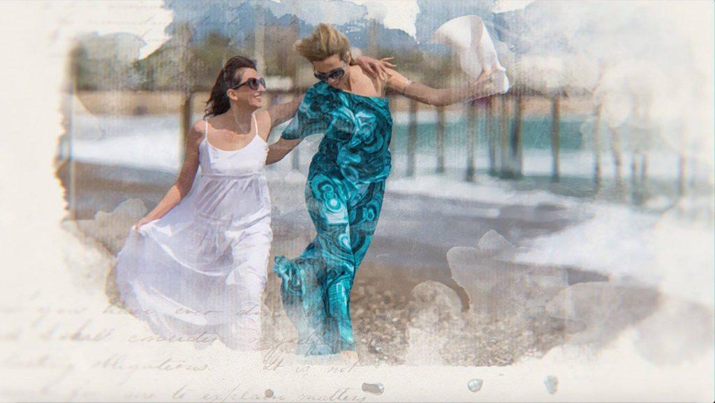 Duas mulheres caminhando sobre a areia do mar. Ambas estão vestindo um vestido longo, sendo um na cor branca e o outro na cor azul. Elas também usam óculos de sol.
