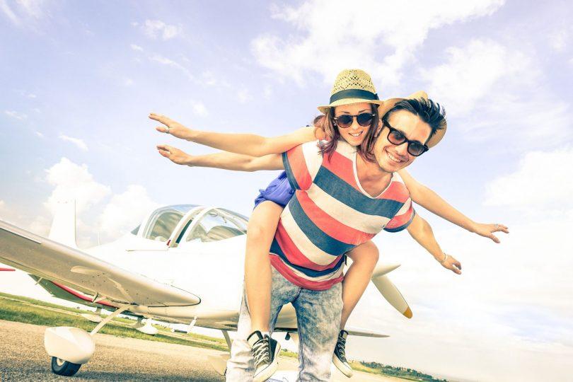 Homem carrega mulher em suas costas, e ambos estão com os braços abertos.