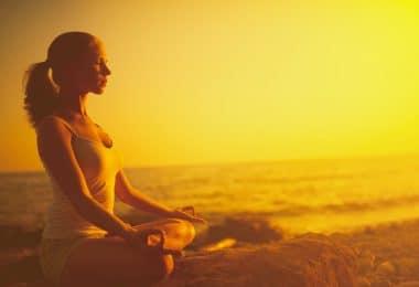 Silhueta de mulher sentada com as pernas cruzadas, meditando e uma praia durante o pôr do sol.