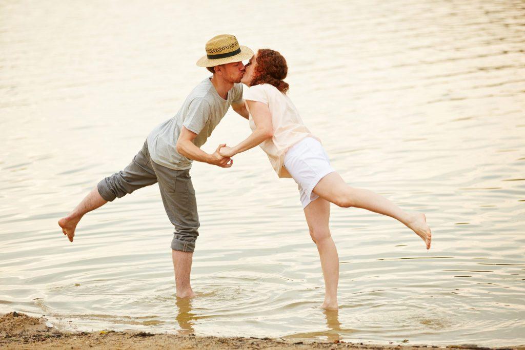 Casal de homem e mulher se beijando na boca dentro da água. Ambos estão em pé, com as pernas meio erguidas. O homem usa um chapéu panamá, calça dobrada e camiseta cinza. A mulher usa uma bermuda branca e uma camiseta salmão.