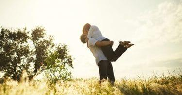Casal se beijando com homem segurando mulher no colo no campo