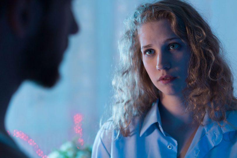 Mulher loira de cabelos cacheados olha para alguém com semblante triste.