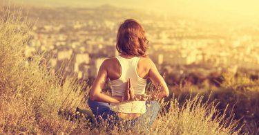 Mulher de costas meditando em campo