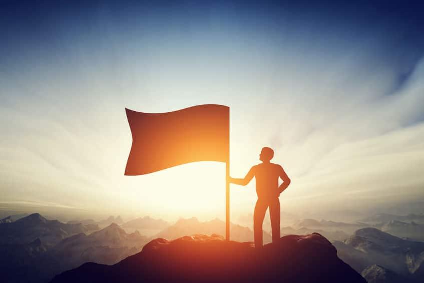 Homem e bandeira no topo de uma montanha, durante o nascer do sol..