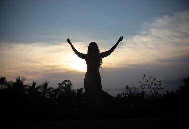 Silhueta de mulher com braços abertos e céu ao fundo