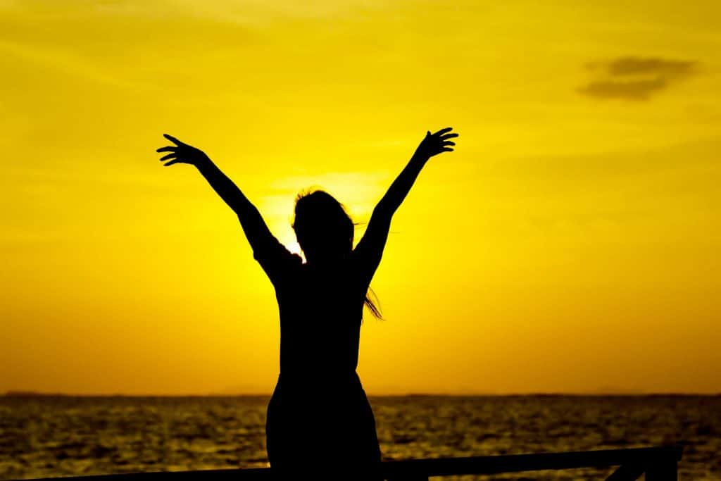 Silhueta de mulher com os braços abertos para cima, na praia enquanto o sol se põe.