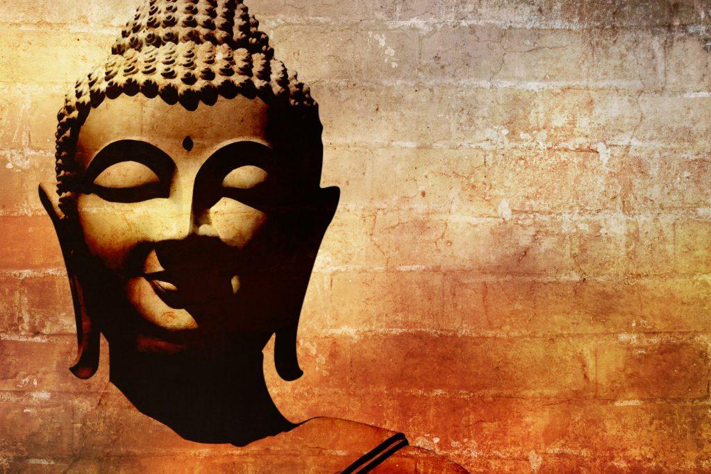 Imagem do rosto de Buda na cor dourada.