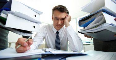 Homem sentado em escritório, com aspecto cansado, cercado por papeis e pastas.