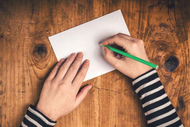 Mãos escrevendo em papel com lápis verde visto de cima
