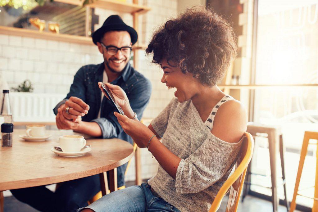 Mulher sorrindo em um café, olhando para um tablet. Ao seu lado, um amigo também ri.
