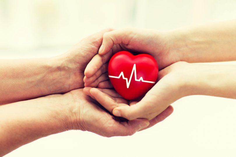 Mãos entregando coração.