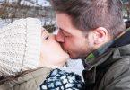 Casal de homem e mulher se beijando na boca. Está frio e eles estão em um parque .