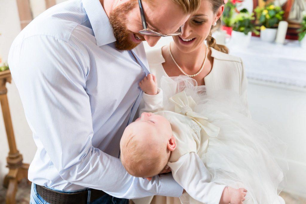 Casal segurando bebê durante batizado