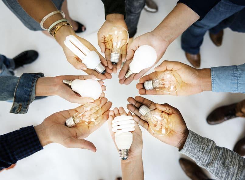 Mãos abertas em círculo segurando lâmpadas acesas.