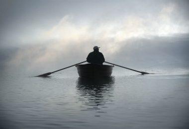 Foto de silhueta de pessoa em um barco, remando no meio do mar com o céu coberto por neblina.