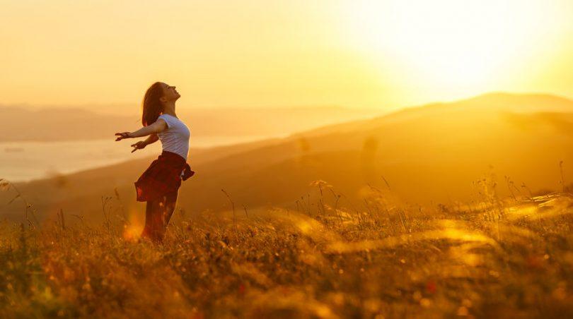Mulher em campo aberto com braços abertos e sol ao fundo