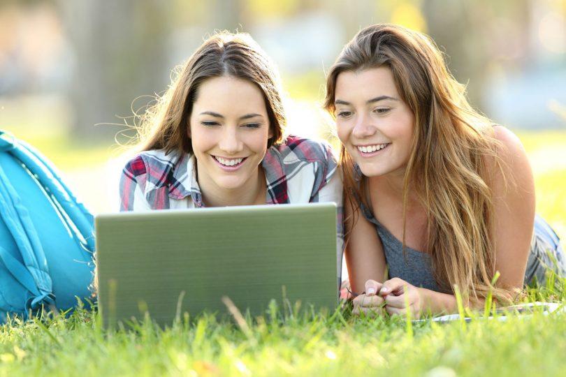 Duas meninas colegiais deitadas na grama, sorrindo e mexendo em notebook..