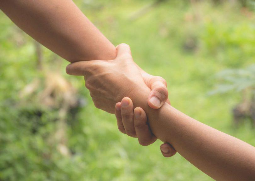 Duas mãos de pessoas diferentes se entrelaçam, simbolizando ajuda.