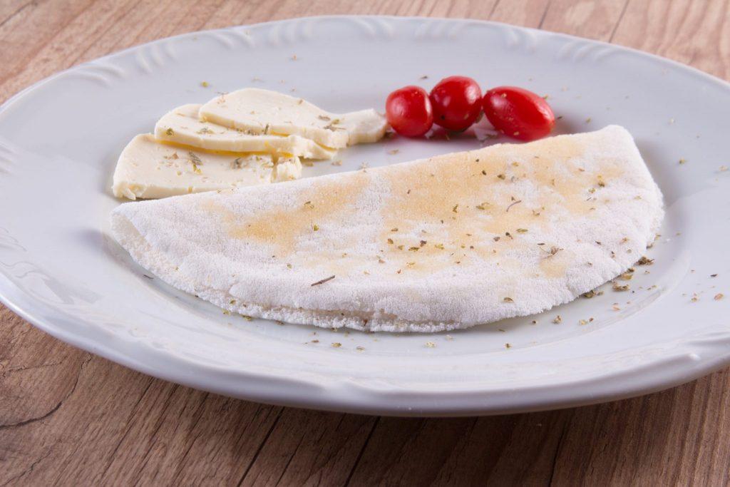 Tapioca pronta para ser servida disposta em um prato branco. Tomates cerejas e pedaços de queijo fresco decoram o prato.