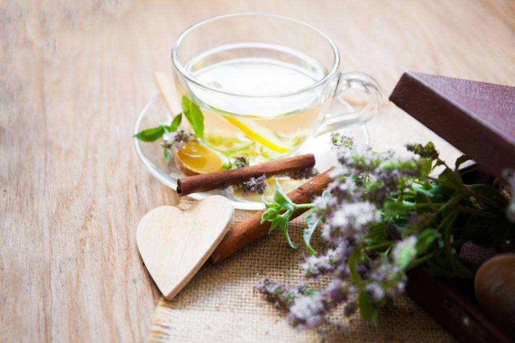 Chá de Valeriana pronto para ser servido em uma xícara de vidro. Ela está sobre um pires decorado com canela de pau e a erva do chá.