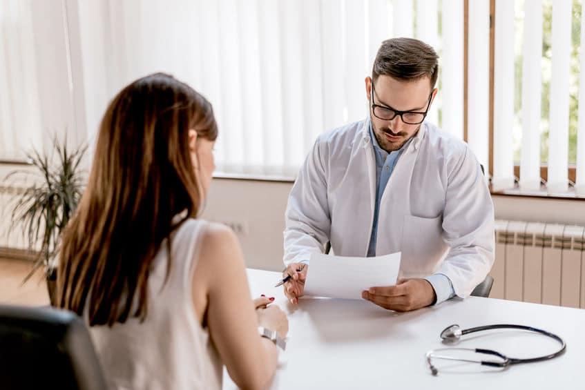 Mulher sentada em consultório enquanto médico analisa os resultados de exames.