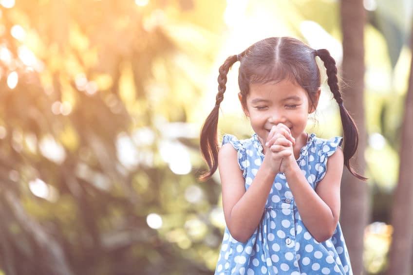 Menina pequena com o cabelo preso em duas trancinhas laterais sorri de olhos fechados enquanto encosta suas duas mãos entrelaçadas na frente de seu rosto.