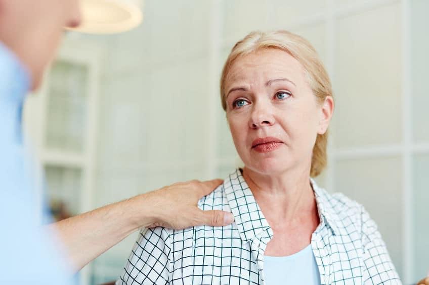Mulher branca, aparentando meia idade, conversando com um homem, que apoia a mão no seu ombro. Aparentemente a mulher está recebendo um conselho.