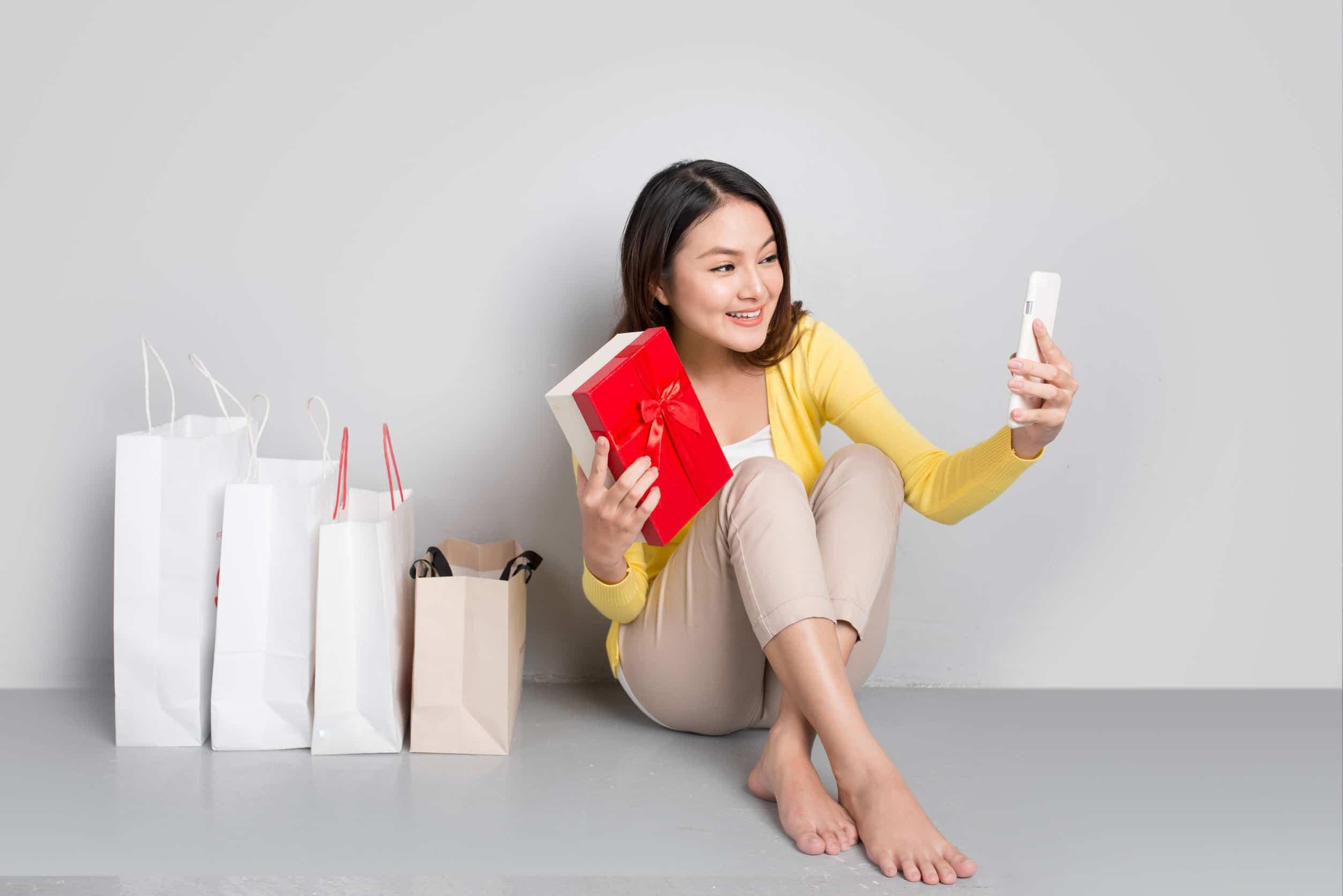Mulher tirando foto com presentes.