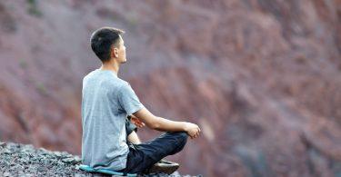 Homem sentado de costas meditando