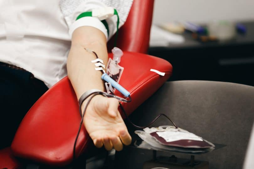 Homem sentado doando sangue