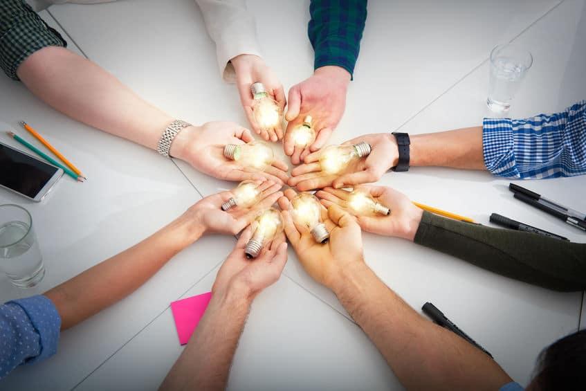 8 pessoas em círculo com um braço esticado cada, e em cada mão existe uma lâmpada acesa, simbolizando ideias.
