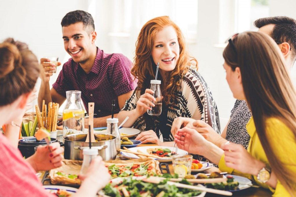 Amigos ao redor de uma mesa com vários pratos veganos.