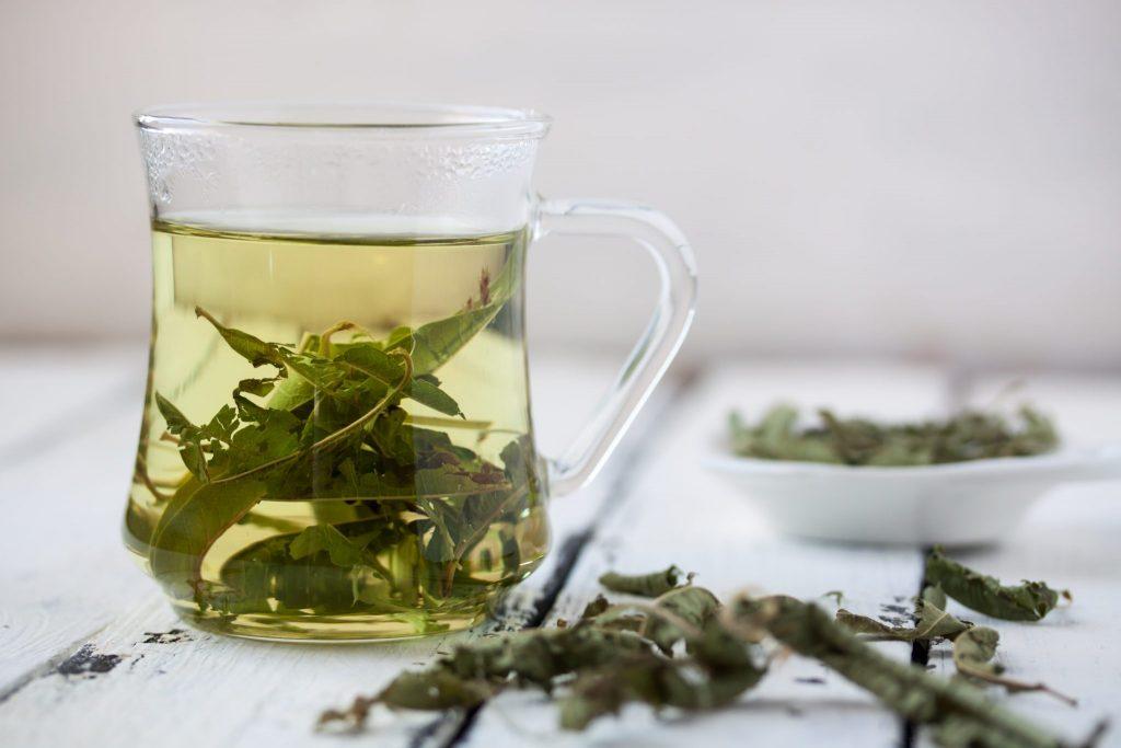 Jarra de vidro com chá de erva cidreira. A jarra está sobre uma mesa de madeira na cor branca. Ao lado da jarra, folhas de cidreira e um pratoo branco também com a erva.