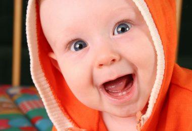 Bebê branco. sem dentes, sorrindo com a boca aberta, embrulhado em uma roupa laranja.
