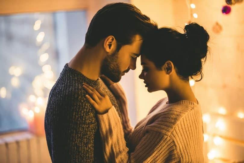 Homem e mulher abraçados, encostando a cabeça um no outro.