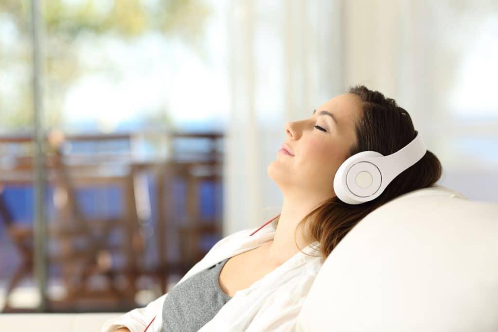 mulher deitada em sofá ouvindo música