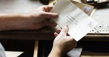 Homem segurando carta escrita.