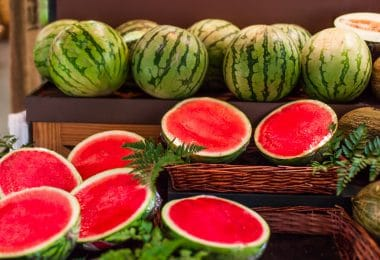 Melancias suculentas maduras em um mercado param no supermercado. frutas de melancia cortadas ao meio e inteiras