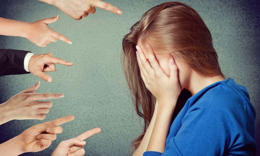 Mulher cobrindo seu rosto com as mãos, enquanto diversas pessoas apontam com o dedo indicador para ela.