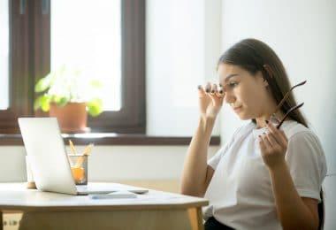 Mulher cansada em ambiente de trabalho.