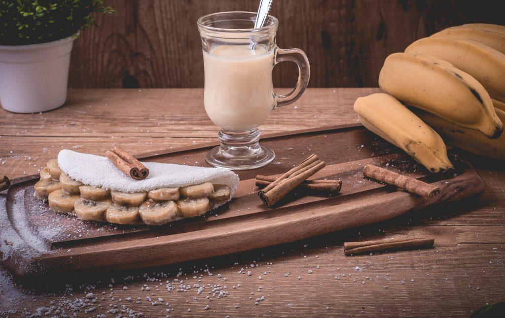 Tapioca recheada com bananas em rodelas. Está disposta em uma tábua de madeira decorada com canelas, bananas e um copo com suco.