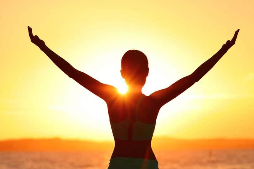 Silhueta de mulher com os braços abertos de frente para o o sol nascendo.