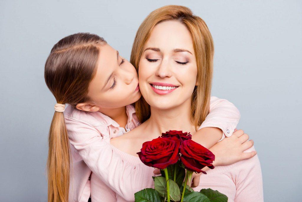 Menina abraça mulher por trás e dá um beijo em sua bochecha direita. A mulher segura um pequeno buquê de rosas.