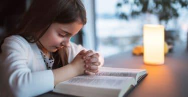 Menina pequena orando debruçada em cima de uma bíblia.